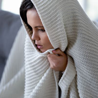 Cold woman wrapped in blanket